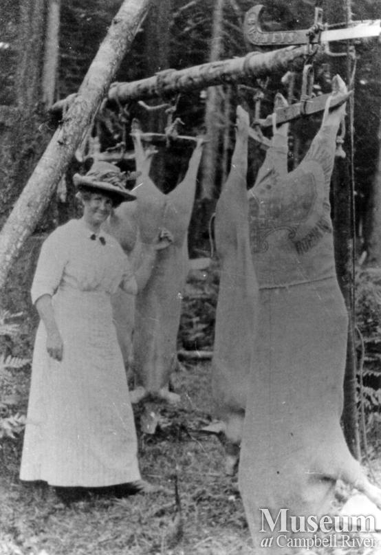 Mrs. James A. Nixon of Twin Islands with slaughtered pigs
