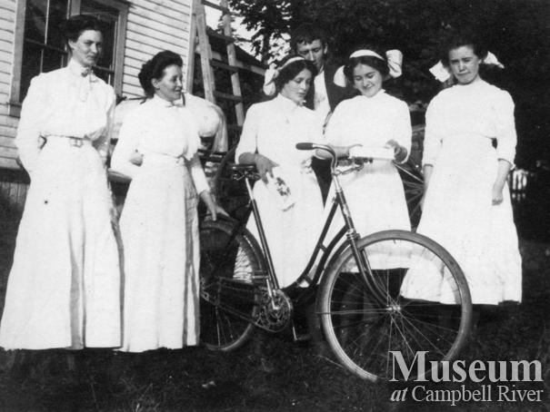 Group of women with bicyle in the Yeatman's back yard, Quadra Island
