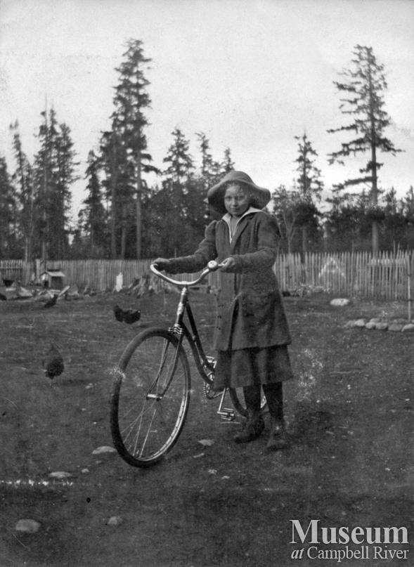 Possibly a member of the Joyce family with her bicycle, Quadra Island