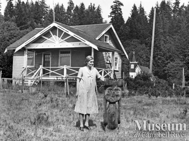 Mrs. Knox with a carving at the Cape Mudge Village, Quadra Island