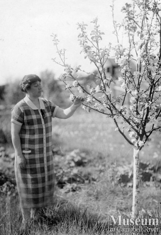Agnes Twidle admiring blossoms on a tree in her garden at Granite Bay