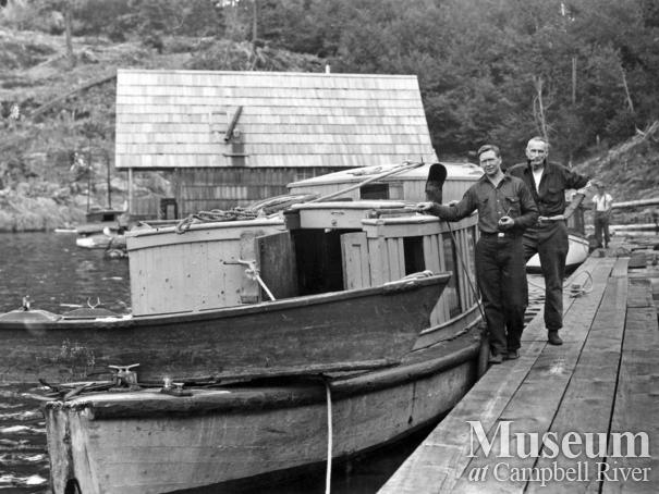 Wood and Armitage beside their boat at Refuge Cove