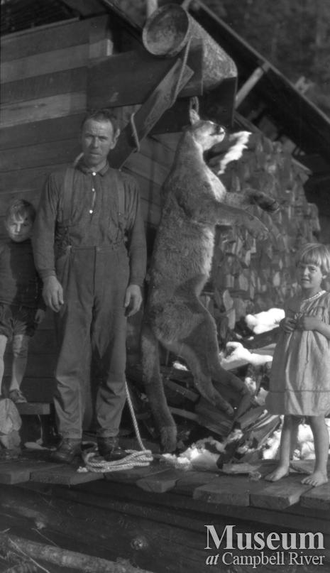 August Schnarr with children on his porch with dead cougar 1920's