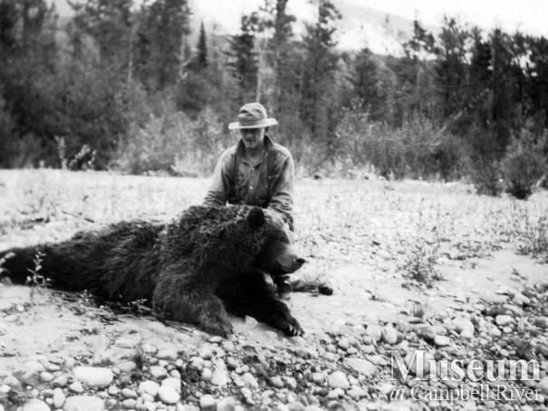 Jim Stanton with dead grizzly bear, Knight Inlet, B.C.