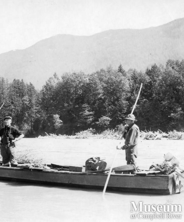 Two men poling up the Kleena Kleene River at the head of Knight Inlet