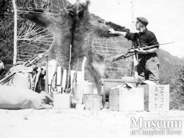 Hunter with grizzly bear hide and hunting equipment