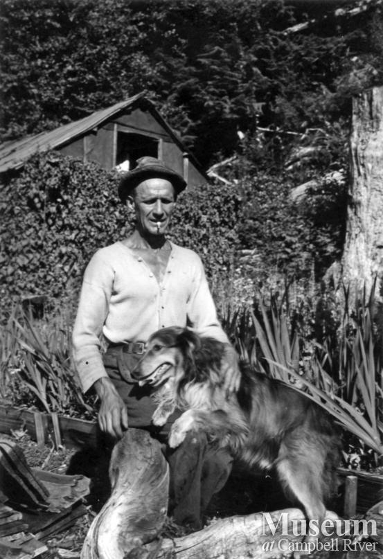 """Slim"" and his dog at his homestead at Ramsey Arm"