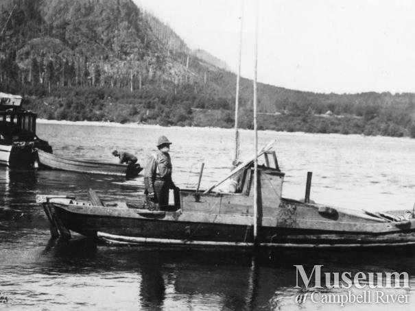 "Alex Burchett on the boat he built and named the ""Orphan Annie"""