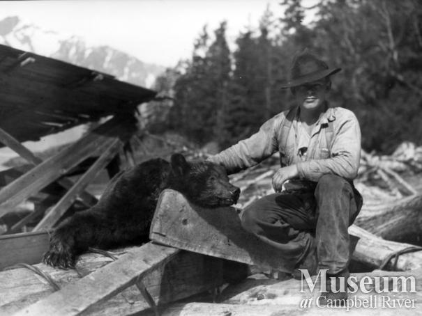 Unidentified man with dead bear