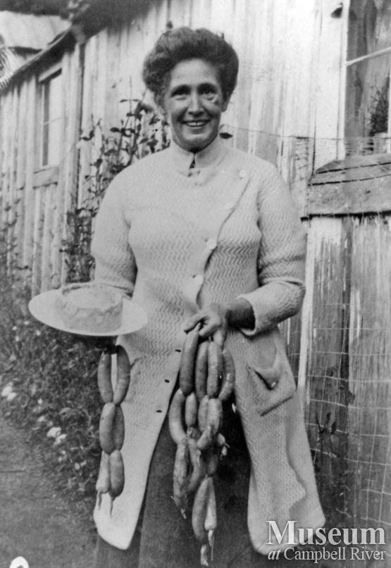 Mrs. James A. Nixon of Twin Islands with string of sausages