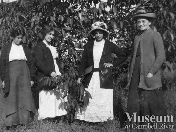 Group of ladies beside the walunt tree at Sunny Side Farm, Quadra Island