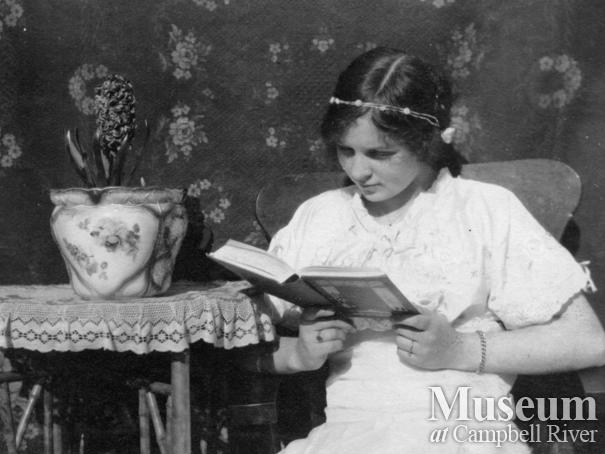 Dot Yeatman reading a book in her home, Quadra Island