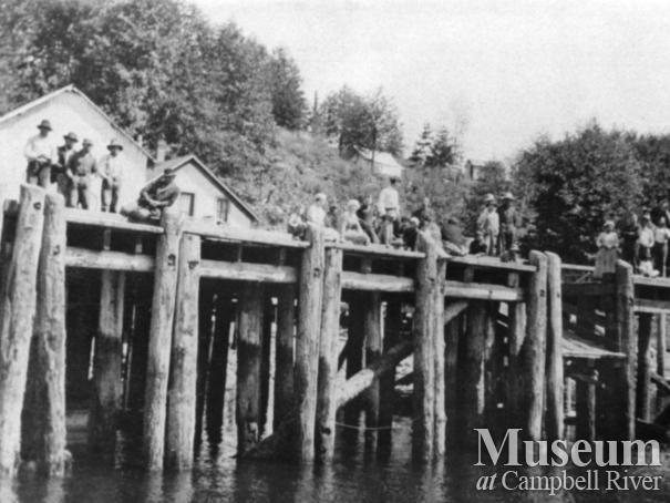 Group of people waving from wharf in front of Quathiaski Cannery